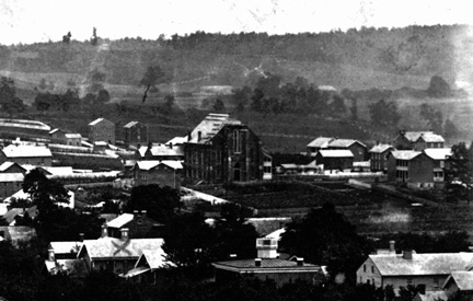 This photograph, from the Historical Society of Carroll County, is one of the earliest known views of Westminster, taken in the late 1860s. St. Paul's United Church of Christ, still under construction, its roof covered with boards and its steeple not yet completed, can be seen near a large as yet undeveloped area that became Belle Grove Square.